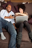 A couple reclining on a sofa sharing a laugh over something on a mobile phone
