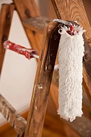 A paint roller hanging from a wood step ladder, close_up