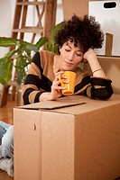 A tired woman taking a coffee break while moving house (thumbnail)