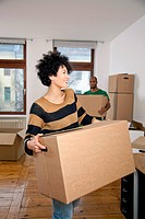 A man and woman carrying moving boxes, focus on woman