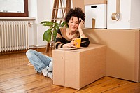 A cheerful woman taking a coffee break while moving house (thumbnail)