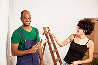 A playful couple having fun while painting apartment