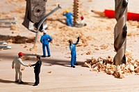 A diorama of a miniature construction site, foreman shaking hands with businessman