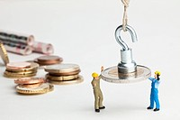 Miniature workmen guiding a hanging two Euro coin down