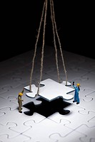 Miniature workmen guiding a hanging puzzle piece into place