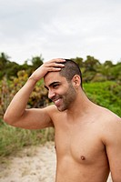 A cheerful young man rubbing his head at the beach