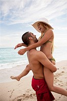 A playful young couple at the beach (thumbnail)
