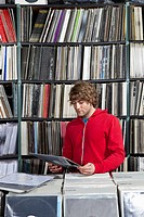 A young man considering a record at a record store