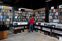 A young man searching through records, rear view