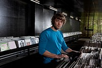 A young man in a record shop, looking at camera