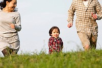 A young boy running in the park in between his mother and father