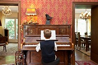 A boy practicing on an old_fashioned upright piano