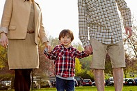 A young boy in between his parents, holding hands (thumbnail)