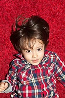 A young boy lying on a red carpet