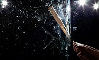 Detail of a man smashing glass with a baseball bat