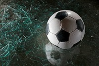 A soccer ball on broken glass