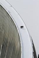 Three people walking above the Zervreila Dam, Switzerland