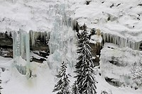 Frozen waterfalls and icicles by mountain side
