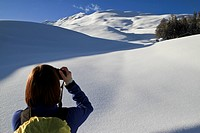Tourist takes photos of snowy landscape