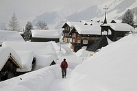 Man strolling through snow covered village (thumbnail)