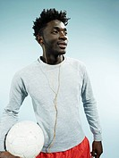 A young man wearing earbuds and holding a soccer ball