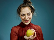 A hip young woman holding an apple and smiling