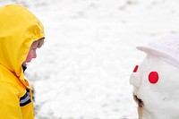 A young boy smiling at a snowman, Kamberg, KwaZulu_Natal, South Africa