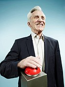 A grinning senior man pushing a red game show buzzer
