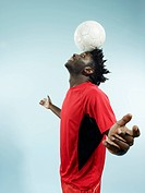 A young man balancing a soccer ball on her forehead