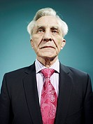 An elegant senior man wearing a suit and bright pink tie