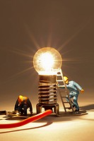 Miniature electrician figurines working on an illuminated light bulb (thumbnail)