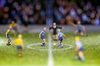 Miniature soccer player figurines at the kick_off of a soccer match