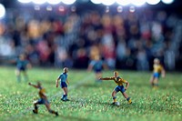 Miniature figurines of two soccer teams playing a soccer match