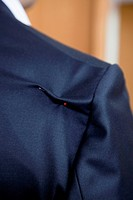 Detail of a pin in the shoulder of a suit jacket