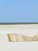 A slanting fence on a beach and the sea in the background (thumbnail)