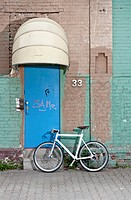 A bicycle in front of a rundown building