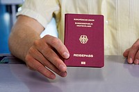Detail of a man holding a German passport