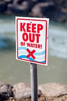 A Keep Out of Water sign posted on a rocky beach (thumbnail)