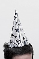 A man wearing a New Year's Eve party hat, top of head