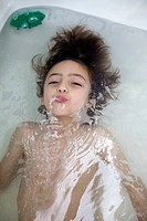A boy underwater in a bathtub blowing bubbles