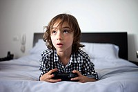 A young boy holding a video game controller looking concentrated