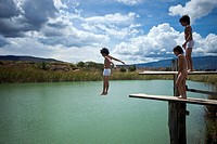 A boy jumping into water while his twin brother and friend watch