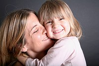 A smiling young girl hugging her mother, close_up