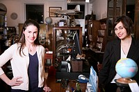Two women standing on opposites sides of a counter in an antiques shop