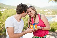 Spain, Mallorca, Young man giving present to teenage girl, smiling