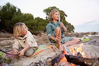 Spain, Mallorca, Children barbecueing sausages on beach