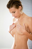 Naked young woman self examining her breasts for cancer