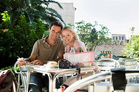 Spain, Mallorca, Palma, Couple sitting at table in cafe, smiling, portrait
