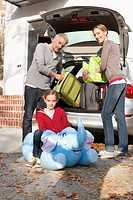 Germany, Leipzig, Family loading luggage into car, smiling, portrait