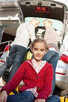 Germany, Leipzig, Family loading luggage into car, smiling